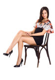Sexy brunette in mini seat on chair Stock Photo