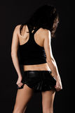 Sexy brunette in mini skirt. Isolated on black Stock Photo
