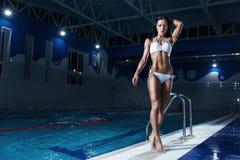 Sexy brunette model in bikini posing at the pool Stock Photo