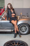 Sexy brunette model in garage Royalty Free Stock Image