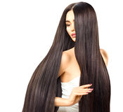 Sexy brunette model girl touching her long shiny hair. Sexy brunette model girl touching her long smooth shiny straight hair Stock Photos