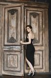 Brunette model girl with a trendy haircut and with bright makeup, in a fashionable black long dress, comes out. Through the vintage wooden doors royalty free stock images