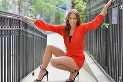 Sexy brunette model poses along iron fence Royalty Free Stock Photography