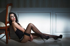 Sexy brunette model sitting on the floor Royalty Free Stock Photography