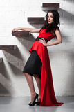 Sexy brunette model wearing red dress near stairway Stock Photography