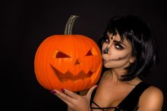 Brunette woman in Halloween makeup and lingerie hold a pumpkin on a black background in the studio. Make-up skeleton, monster. Brunette model woman in Halloween stock images