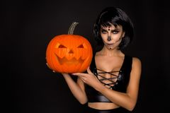 Brunette woman in Halloween makeup and lingerie hold a pumpkin on a black background in the studio. Make-up skeleton, monster. Brunette model woman in Halloween royalty free stock photos