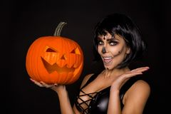 Brunette woman in Halloween makeup and lingerie hold a pumpkin on a black background in the studio. Make-up skeleton, monster. Brunette model woman in Halloween stock photos