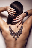 Sexy brunette with naked  back with jewellery Stock Photo