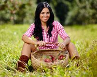 brunette near a basket of apples Stock Photo