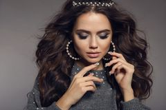 brunette portrait. Beauty makeup. Pearls jewelry set. Curly long hair style. Manicured nails. Sensual girl model with matte royalty free stock image