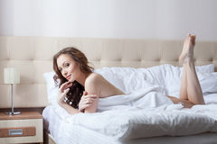 Sexy brunette posing lying on bed in hotel room Stock Image