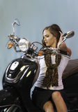 Sexy brunette posing on scooter Royalty Free Stock Photos