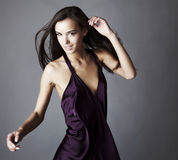 Sexy brunette posing in silk violet dress Stock Photography