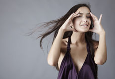Sexy brunette posing in silk violet dress Stock Image