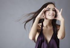 Sexy brunette posing in silk violet dress Stock Image