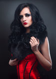 Sexy brunette in red corset fur and long hair in s Royalty Free Stock Photos