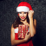 Sexy brunette santa woman holding christmas gift Stock Photo