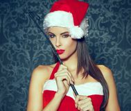 Sexy brunette santa woman with red lips holding whip indoors por. Trait, bdsm Royalty Free Stock Images