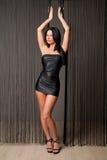 Sexy brunette in short black dress. Studio shot Royalty Free Stock Photo