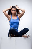 Sexy brunette sit in jeans and blue tank top. Young pretty brunette woman sit in jeans and blue tank top Royalty Free Stock Photography