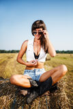 Sexy brunette sitting on straw bale Stock Image
