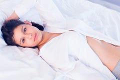 brunette smiling at camera on bed Stock Images
