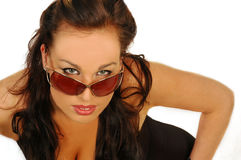 Sexy brunette in sunglasses. Smiling sexy young woman wearing sunglasses against a white background with space on the right for text Royalty Free Stock Photography