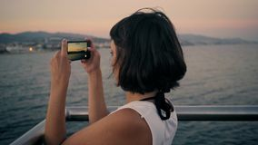 Sexy brunette takes photo of sunset stock video