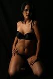 Brunette in underwear. Brunnette in black underwear and black background stock image