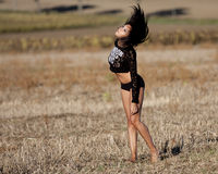 Sexy brunette walking with wind in the hair. The wind blows in the black hair of a young woman. Closed eyes, she moves barefoot in a field of stubble. She wears Royalty Free Stock Photo