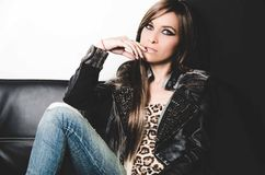 brunette wearing denim jeans, leopard top and leather jacket, sitting in sofa posing seductively for camera.  Royalty Free Stock Photography