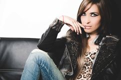 brunette wearing denim jeans, leopard top and leather jacket, sitting in sofa posing seductively for camera.  Stock Photography