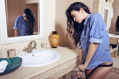 Sexy brunette wearing lingerie and jeans shirt posing in bathroom Royalty Free Stock Images