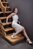 Sexy brunette in a white dress sitting on wooden stairs. Stock Photos