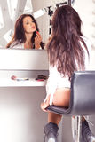 Sexy brunette in white shirt sitting on the visage's by the mirr Stock Image