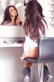 Sexy brunette in white shirt sitting on the visage's by the mirr Royalty Free Stock Photos