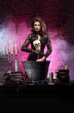 A brunette witch making poison Royalty Free Stock Photography