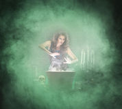 Sexy brunette witch making poison in the dungeon Stock Photo