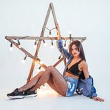 Sexy brunette woman in a beautiful jeans in the studio. Wooden star with lights Stock Photos