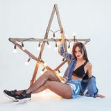 Sexy brunette woman in a beautiful jeans in the studio. Wooden star with lights Stock Images