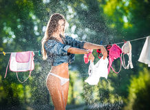 brunette woman in bikini and shirt putting clothes to dry in sun. Sensual young female with long legs putting out the washing Royalty Free Stock Photography