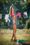 brunette woman in bikini and shirt putting clothes to dry in sun. Sensual young female with long legs putting out the washing stock photography