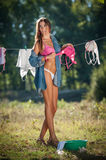 Sexy brunette woman in bikini and shirt putting clothes to dry in sun. Sensual young female with long legs putting out the washing Royalty Free Stock Image