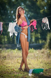 Sexy brunette woman in bikini and shirt putting clothes to dry in sun. Sensual young female with long legs putting out the washing Royalty Free Stock Photography