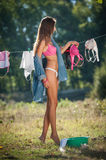 Sexy brunette woman in bikini and shirt putting clothes to dry in sun. Sensual young female with long legs putting out the washing. To dry in sunny day. Perfect Stock Photo