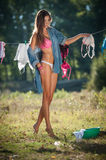Sexy brunette woman in bikini and shirt putting clothes to dry in sun. Sensual young female with long legs putting out the washing Royalty Free Stock Photos
