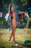 Sexy brunette woman in bikini and shirt putting clothes to dry in sun. Sensual young female with long legs putting out the washing Stock Image