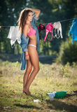 Sexy brunette woman in bikini and shirt putting clothes to dry in sun. Sensual young female with long legs putting out the washing. To dry in sunny day. Perfect Stock Images