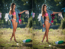 Sexy brunette woman in bikini and shirt putting clothes to dry in sun. Sensual young female with long legs putting out the washing. To dry in sunny day. Perfect Royalty Free Stock Photography